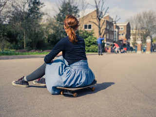 Woman sitting on skateboard in the park