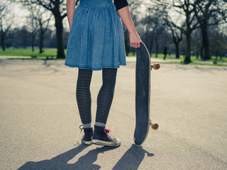 Young woman standing in the park with a skateboard
