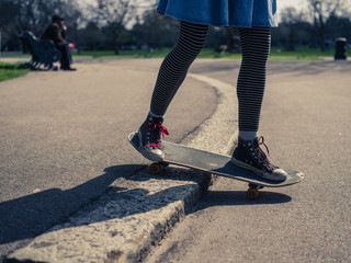 Young woman doing skateboard trick on curb