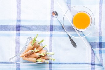 Baby carrots juice glass with raw ingredient