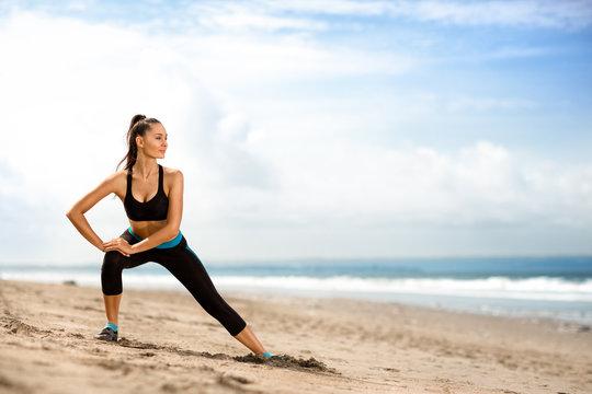 sportswoman doing exercises on beach