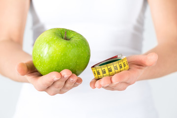 Woman's hands with green apple and measuring tape. Dieting