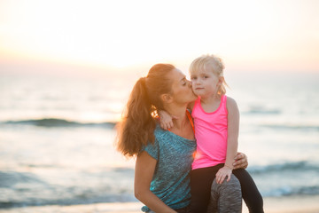 Healthy mother and baby girl kissing on beach in the evening