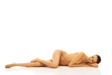 Nude woman lying on belly with closed eyes