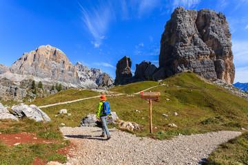 Woman tourist on path to Cinque Torri in Dolomites Mountains