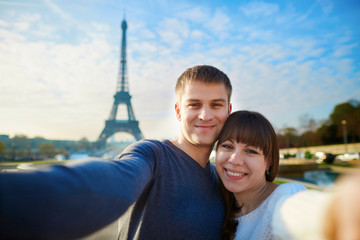 Happy couple of tourists taking selfie in Paris