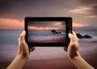 Take a landscape picture with a tablet PC during te sunset