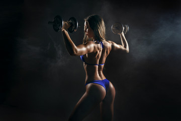 Fitness girl do workout with dumbbells on dark background