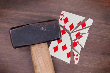 Hammer with a broken card, ten of diamonds