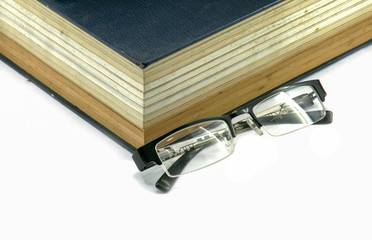 Old text book or bible with eyeglasses