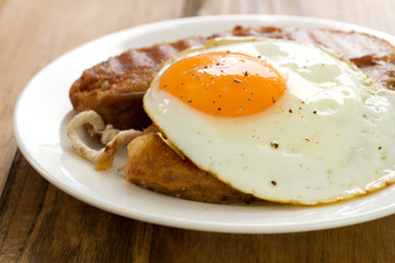 fried alheira with egg on white plate
