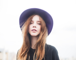 beautiful sexy girl with long hair in a hat on a sunny day