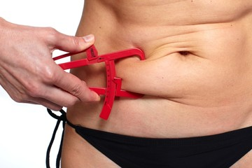 Woman measuring fat belly.