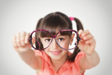little girl holding eyeglasses, health eyesight concept.Soft fo