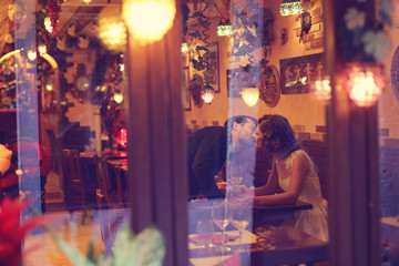 Bride and groom sitting on table at restaurant