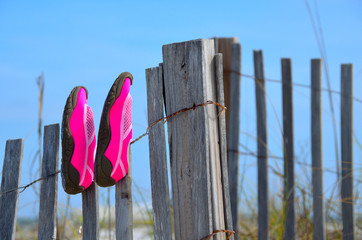 Beach swim shoes drying on weathered beach fence