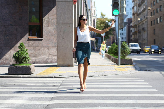 Business woman crossing the road outside