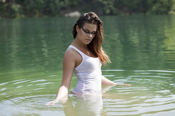Young brunette woman in t-shirt in a river water