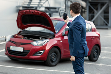 businessman making photo on phone of breakdown car for insurance