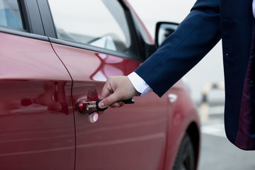 Closeup of businessman hand opening car door