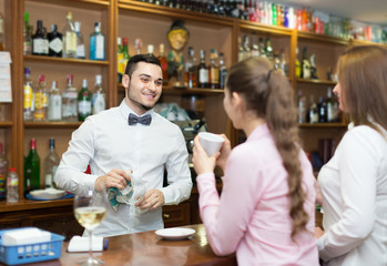 Two girls flirting with barman .