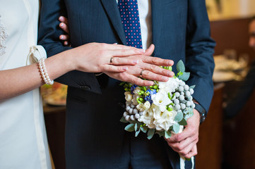 Hands of the bride and groom with the rings lying on the bridal