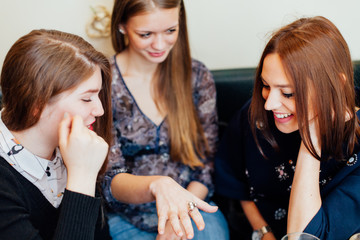 girl showing engagement ring to friends