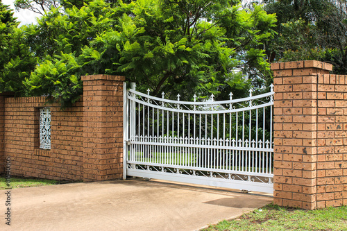 White wrought iron driveway entrance gates in brick fence for Brick and wrought iron fence