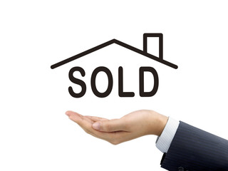 sold house word holding by businessman's hand