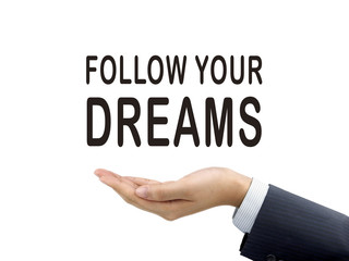 follow your dreams words holding by businessman's hand
