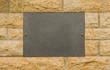 Leere Gedenktafel aus schwarzem Granit in Granitmauer