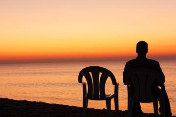 Obraz Man sits on chair alone in sunset - fototapety do salonu
