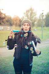 young beautiful brunette woman blowing bubble soap
