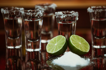 shots of tequila with lime and salt on a wooden table bar