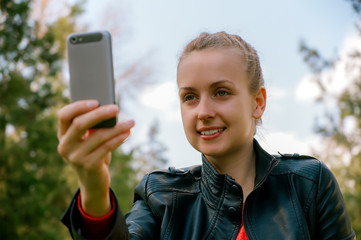 Young woman making selfie with smartphone in green park