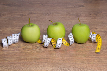 three green apples and measure tape on table