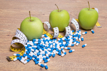 diet concept - apples, pills and measure tape on table