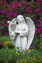 White marble statue of angel in flower garden