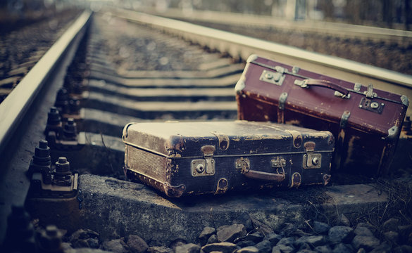 Two old fashioned a suitcases on railroad tracks