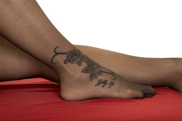 woman legs with tattoo on foot in black stockings on red sheet c