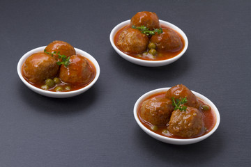 Delicious meatballs with peas and sauce on a slate table