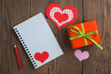 Notebook with gift, pencil and hearts on old wooden table