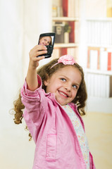 cute little girl using cell phone taking a selfie