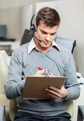 Customer Service Representative Writing On Notepad