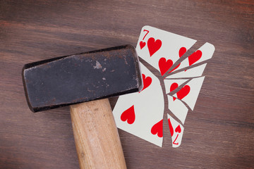 Hammer with a broken card, seven of hearts