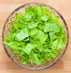 Fresh salad leafs in glass plate on a wooden board