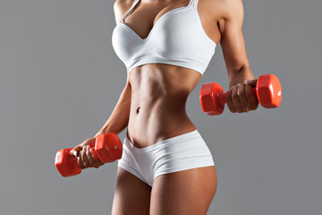Torso of a young sexy woman lifting dumbbells on gray background