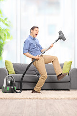 Delighted guy playing guitar on the vacuum cleaner