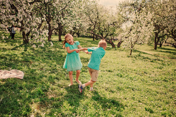 happy siblings dancing in spring apple garden