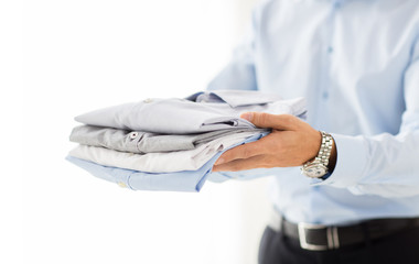Wall Mural - close up of businessman holding folded shirts